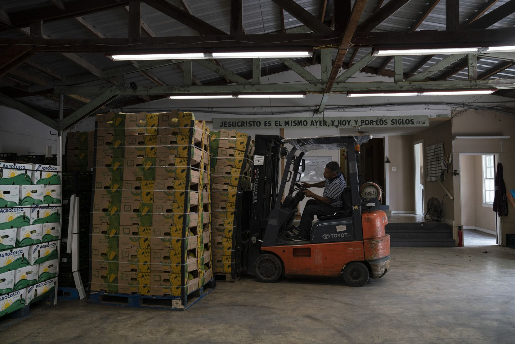Lucio Ramirez, 53, moves jackfruit pallets into the Border Missions warehouse in Hidalgo. The produce will be distributed to local residents and to people in Reynosa, Mexico.