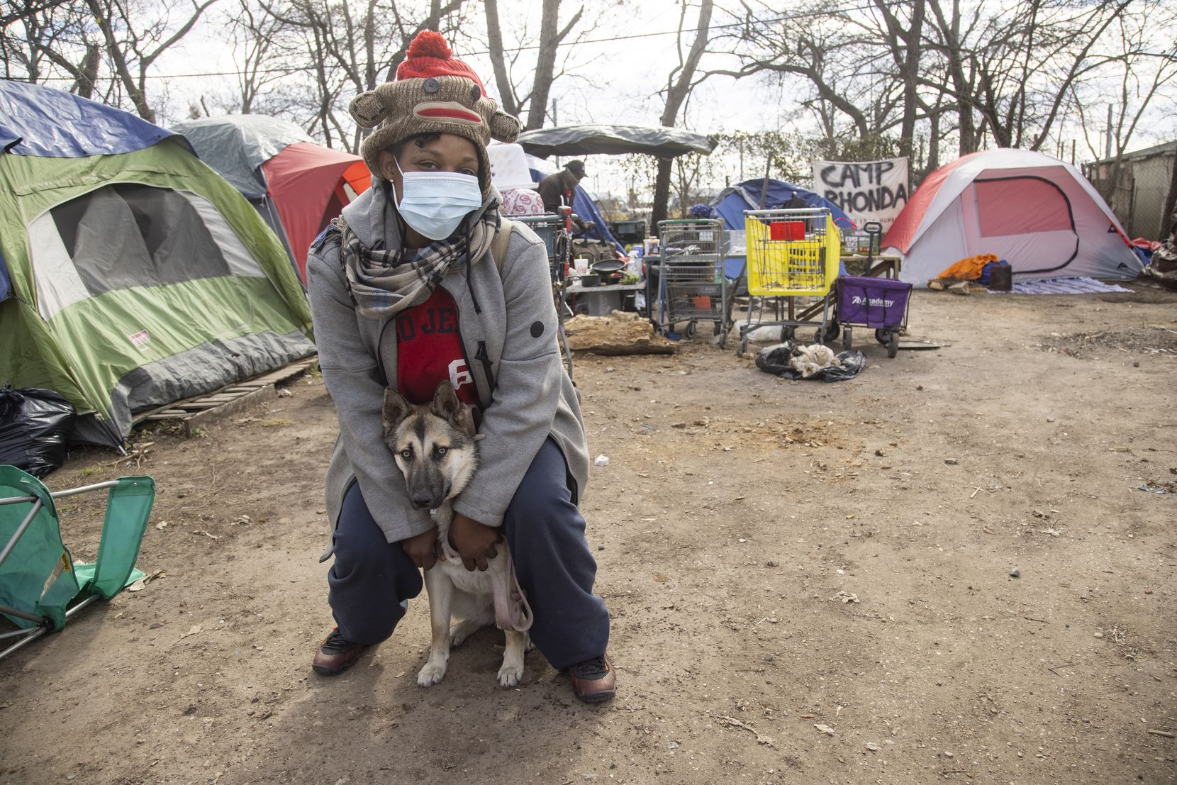 Angel Sharpe poses with her dog Bella at Camp Rhonda, a homeless encampment located on a lot along I-45, on Friday, Feb. 5, 2021 in South Dallas. Sharpe had been living at Camp Rhonda for a week. Last week, city officials sent a notice to the owner of the property, Johnny Aguinaga, stating that the lot needed to be empty by Feb. 6. (Juan Figueroa/ The Dallas Morning News)