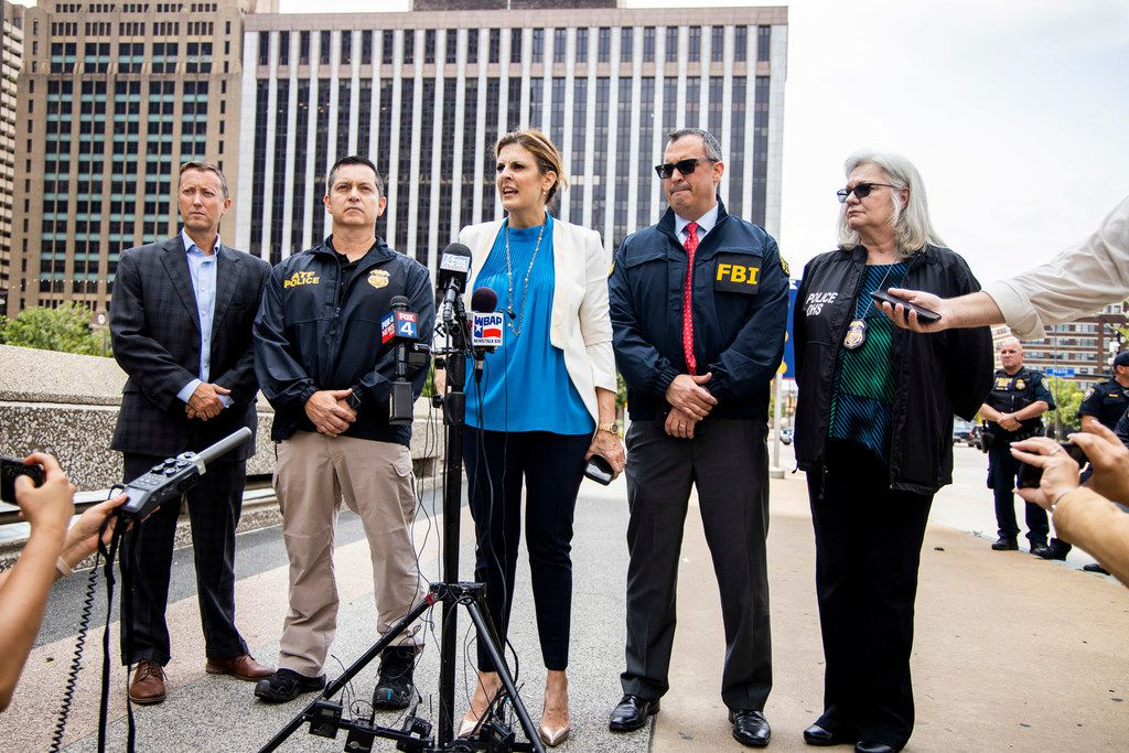 Erin Nealy Cox, center, U.S. Attorney for the Northern District of Texas, addresses the media ,along with FBI Special Agent in Charge Matt DeSarno, second right, after a man was shot and killed after shooting at the federal courthouse in Dallas.