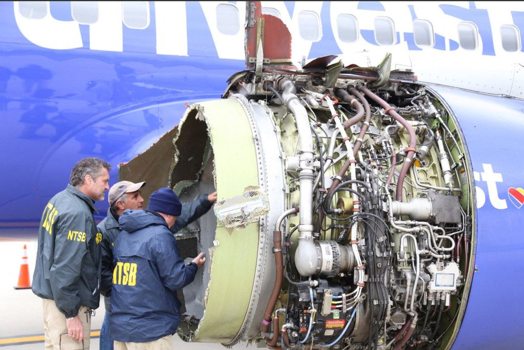 NTSB investigators examine damage to the engine of the Southwest Airlines plane that made an emergency landing in Philadelphia. MUST CREDIT: NTSB handout