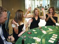 Monument Realty agents (from right) Angela Cunningham, Shannon Brownstein, Annmarie Eidman and owner Eddie Burns celebrated a winning Blackjack hand as they gathered for a casino night party at Twelve Cowboys Way in Frisco in August.
