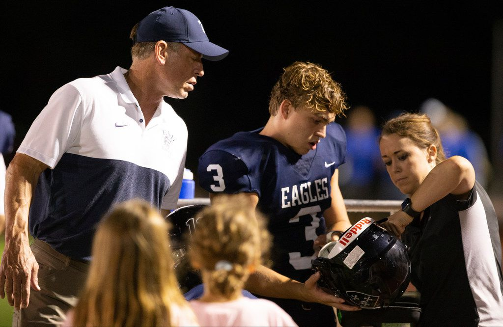 ESD quarterback Preston Morway (#3) gets his helmet worked on by trainer Emily Gill as former Dallas Cowboys quarterback and part-time QBs coach Troy Aikman watches during the Episcopal School of Dallas game against Trinity Christian Academy on Friday, Aug 30, 2019. (Riley Breaux/Special Contributor)