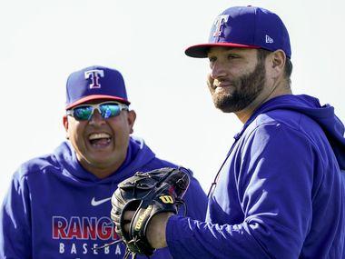 El coach de pitcheo de los Texas Rangers, Julio Rangel, sonría mientras observa el trabajo del lanzador Lance Lynn (der), el 12 de febrero de 2020 en Surprise, Arizona