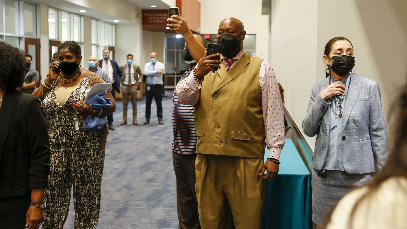 Dallas ISD school board member Maxie Johnson (center) and DISD employees record opponents of mask mandates during a Dallas ISD school board meeting on Aug. 26, 2021, in Dallas.