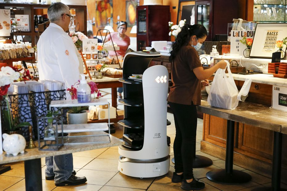 """La Duni co-owner Taco Borga, on left, tells a story of one woman who saw his robots on social media and wanted to bring her kids """"if the robots are working today."""" He smiles: """"I said 'Miss, let me explain to you one thing: The whole thing about a robot is they work 24/7.' ... As long as we have power, the robots will be working."""""""