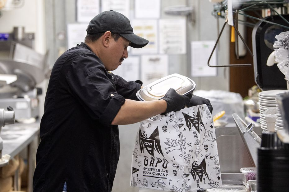 Miguel Acosta, a prep cook at Greenville Avenue Pizza Company, loads an Uber Eats pick-up order into a bag on March 19, 2020 in Dallas.
