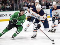 Dallas Stars center Mattias Janmark (13) and Edmonton Oilers defenseman Kris Russell (4) compete for the puck in the first period of an NHL hockey game, Monday, Dec. 16, 2019, in Dallas.