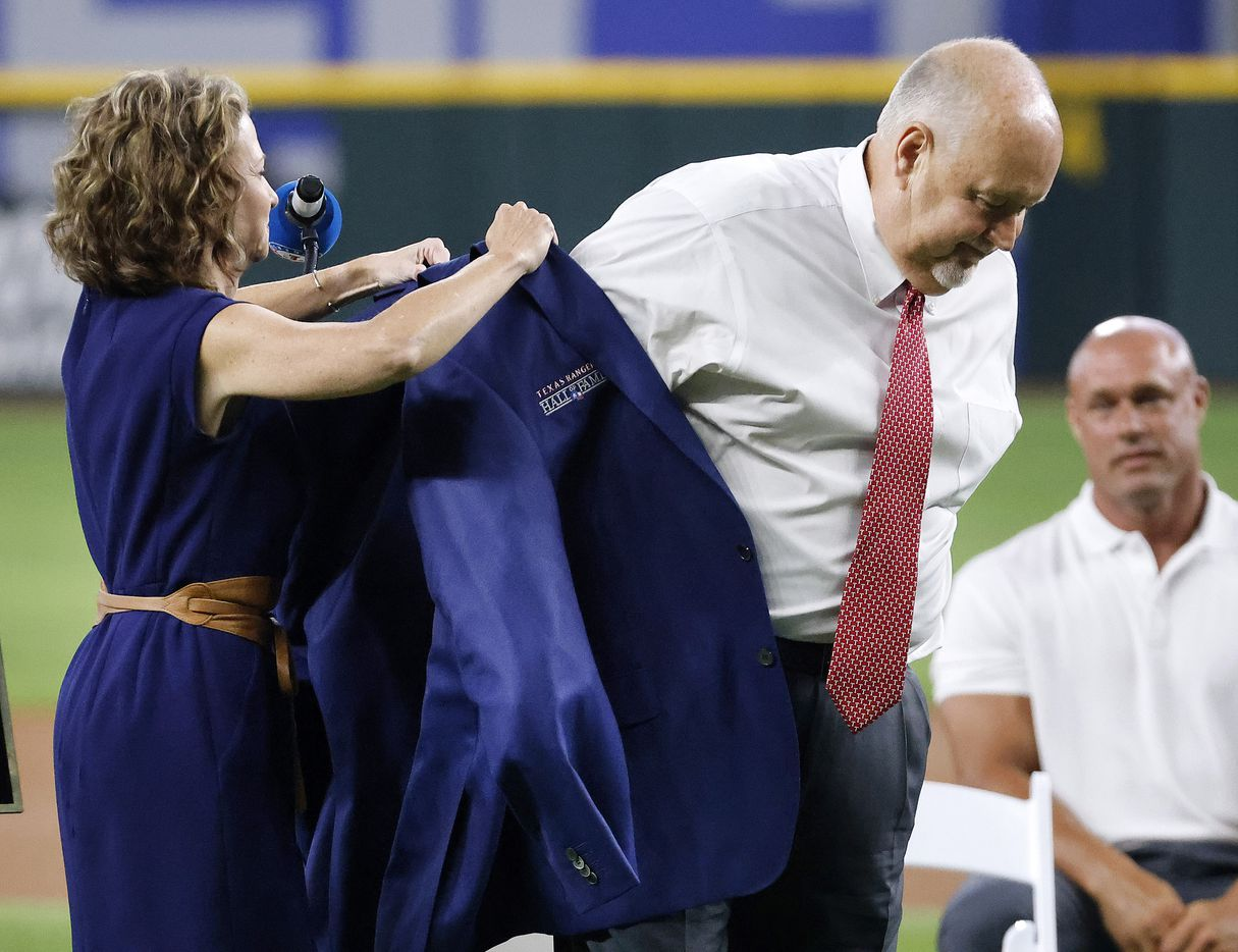 Texas Rangers executive vice president and public address announcer Chuck Morgan receives help with his blue jacket from his presenter and Rangers CFO Kellie Fischer during the Texas Rangers Baseball Hall of Fame induction ceremony at Globe Life Field in Arlington, Saturday, August 14, 2021.(Tom Fox/The Dallas Morning News)