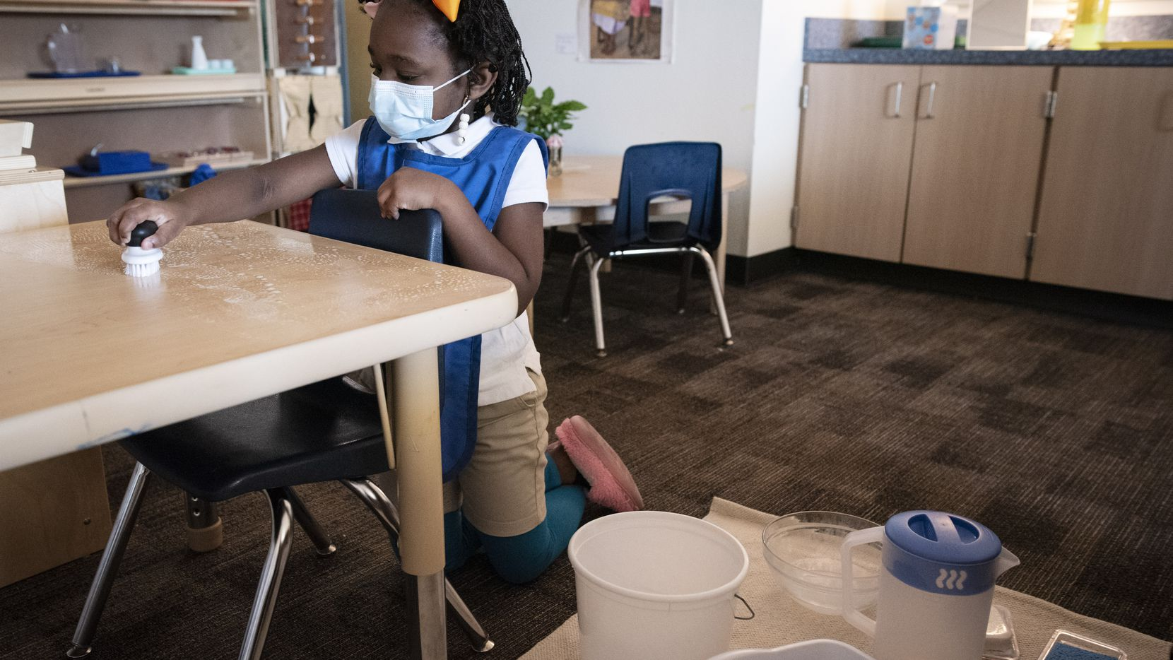Primary student Erin Choice scrubs a table with soap as she works on practical life skills such as independence, order, process and organization, part of the Montessori program at Lake Ridge Elementary in Cedar Hill, on Wednesday, Nov. 18, 2020.