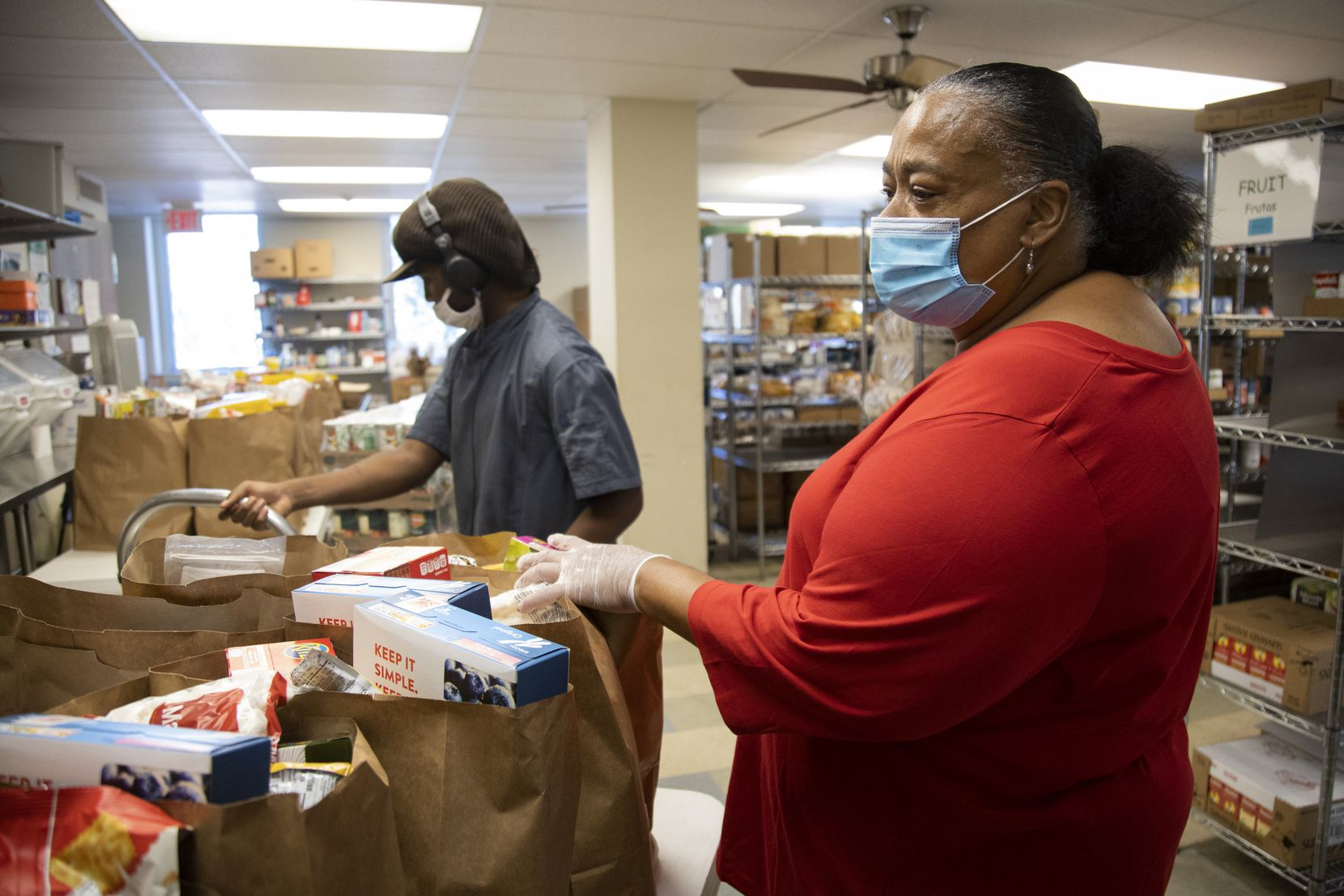Dawn Shepard, Rangers fan and Broadway Baptist Church's community center director, looks over bags of food ready for distribution from the food pantry at the Fort Worth church.