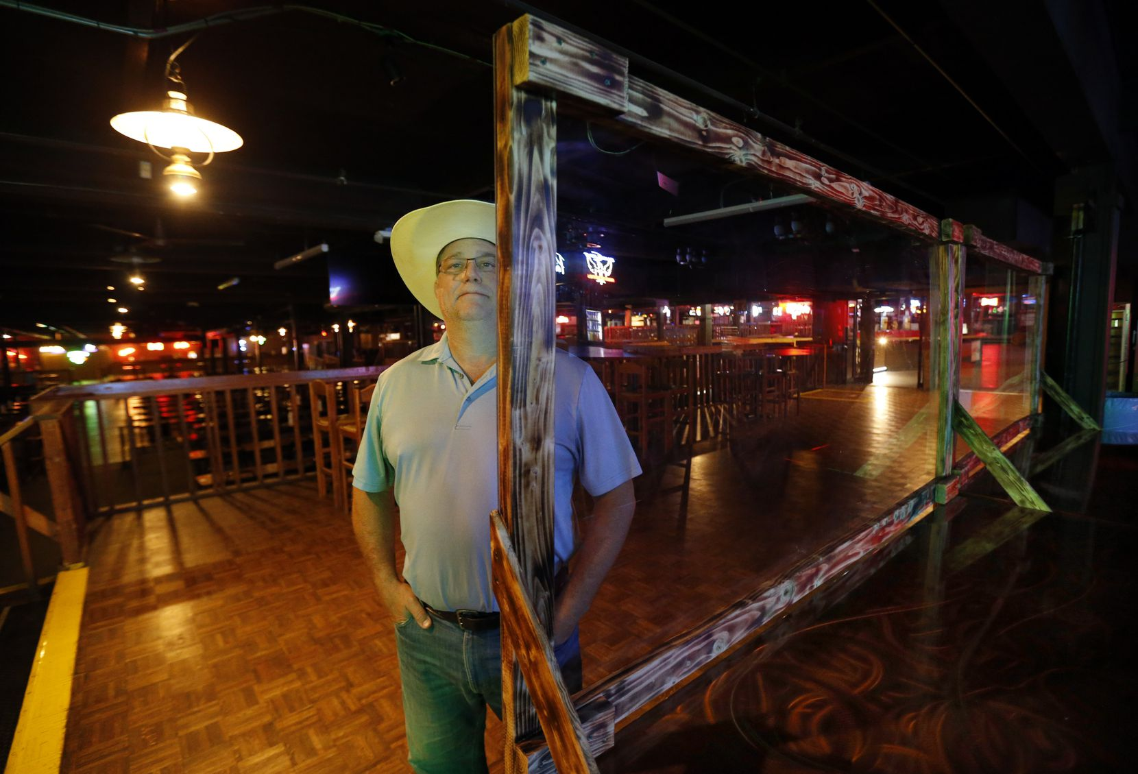 Billy Bob's Texas' Ambassador of Fun Marty Travis — also known as the general manager — stands behind a plexiglass wall separating patrons from the food service in the Fort Worth entertainment venue.