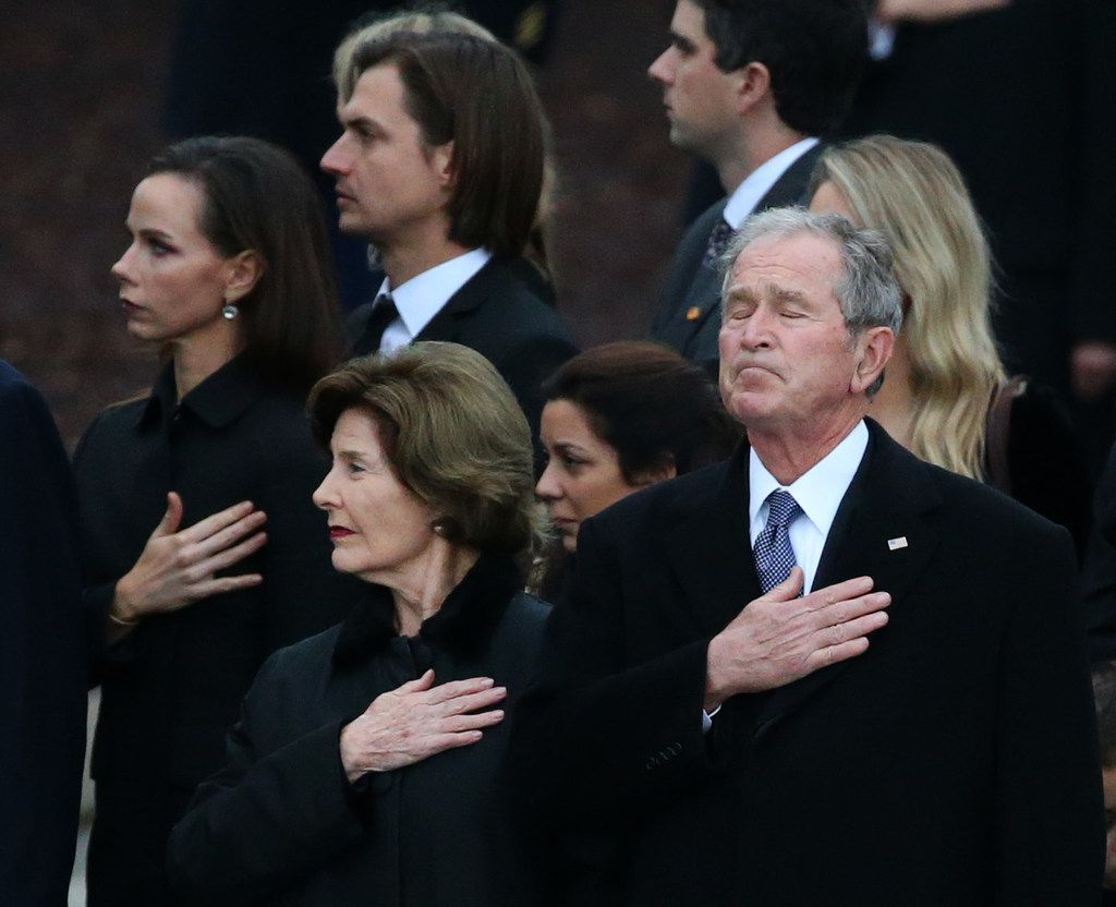 Former President George W. Bush reacts alongside his wife Laura Bush as the flag-draped casket of his father former President George H.W. Bush is carried by a joint services honor guard from the funeral train pulled by a custom-painted Union Pacific Locomotive 4141 to his final resting place at the George H.W. Bush Presidential Library Center on Texas A&M University campus in College Station, Texas on Thursday, Dec. 6, 2018.