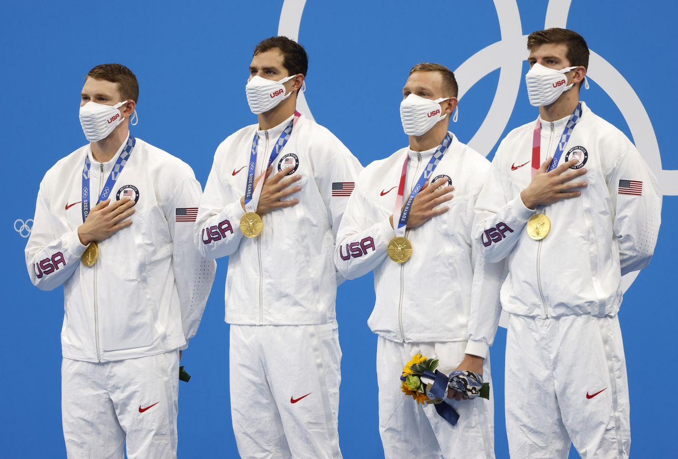 (Left to right) USA's Ryan Murphy, Michael Andrew, Caeleb Dressel, and Zach Apple stand as the national anthem is played during the men's 4x100 meter medley relay medal ceremony at the postponed 2020 Tokyo Olympics at Tokyo Aquatics Centre, on Sunday, August 1, 2021, in Tokyo, Japan. USA earned a gold medal, setting a new world record with a time of 3:26.78. (Vernon Bryant/The Dallas Morning News)