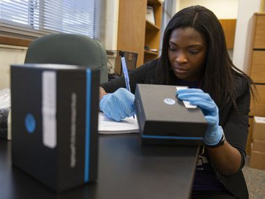 STEAM coordinator Ronessa Hollingsworth prepares paperwork for a WiFi hotspot provided by DISD for a student at Young Women's STEAM Academy at Balch Springs on April 24, 2020 in Dallas. A district survey found that 30% of families responded that they didn't have internet at home.