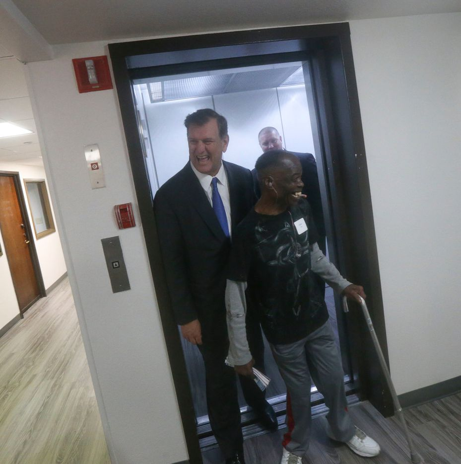 (From left) Dallas Mayor Mike Rawlings exits an elevator with resident Hilton Gray at the St. Jude Center, in Dallas on Wednesday, October 10, 2018. The mayor received a tour of a different resident's apartment. (Daniel Carde/The Dallas Morning News)