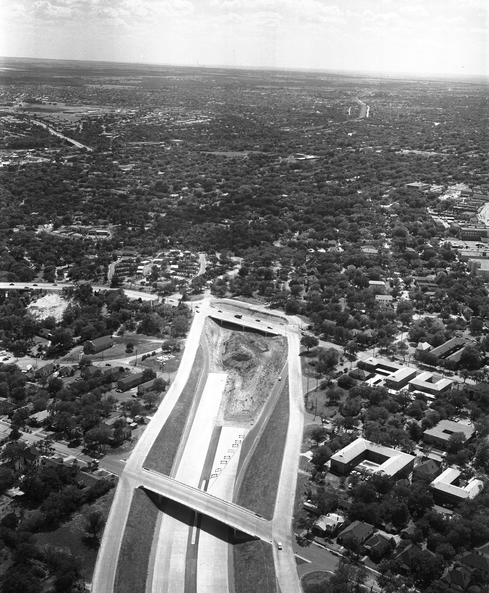 This 1959 photo shows how the construction of R.L Thornton Freeway, I-35E, cut directly through neighborhoods just south of downtown Dallas, demolishing homes and businesses as the work rolled on. This view, facing south, was taken at the point that the construction had proceeded to the intersection with Marsalis Avenue, severing connections between the east and west neighborhoods of Oak Cliff.