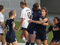 Euphoria filled the air as a celebration broke out after Flower Mound's Marianne Baltmanis (4) facing camera, receives a hug from teammate Bella Hernandez (9) as other teammates move in to congratulate her first half goal to break a scoreless tie in their match against Flower Mound Marcus. Paige Dickson (13) of Flower Mound Marcus can only turn her back to the celebration. The two teams played their Class 6A Region 1 final girls soccer playoff game at McKinney ISD Stadium in McKinney on April 9, 2021.
