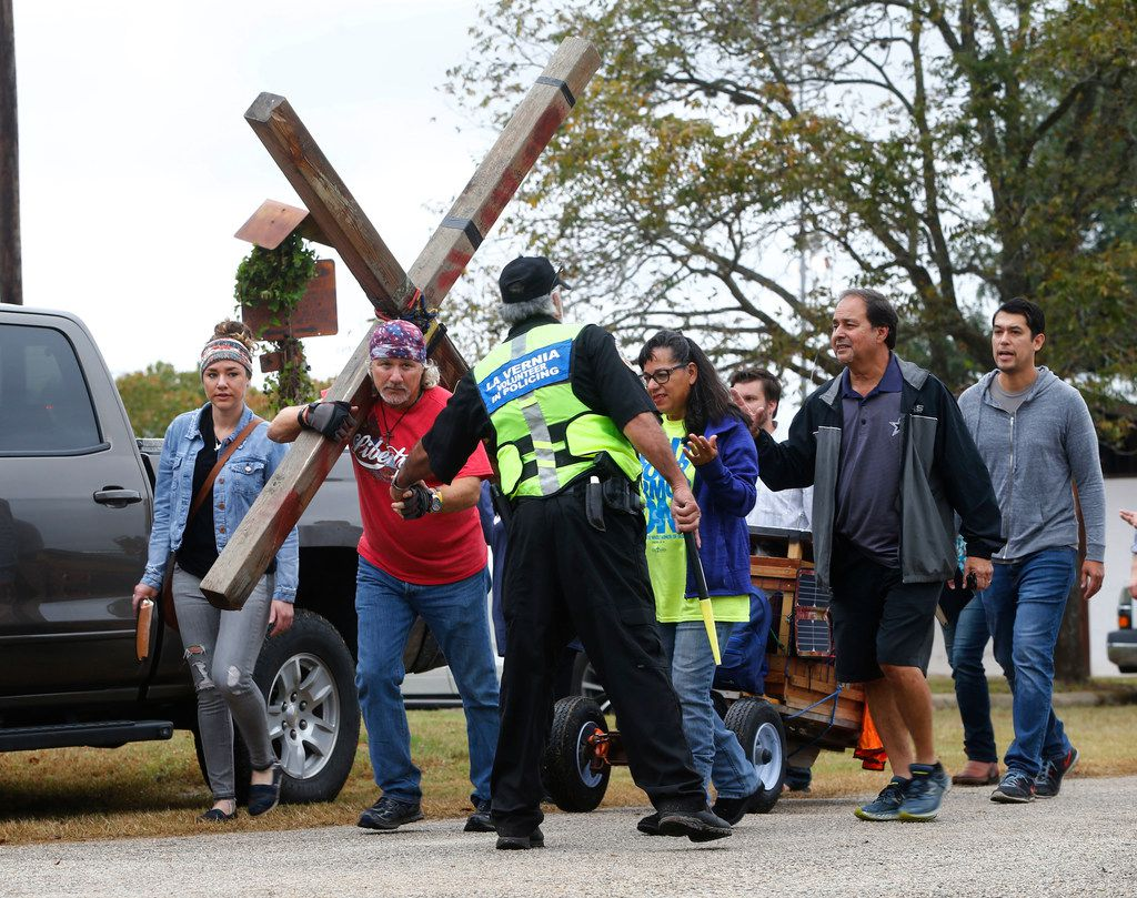 A man carrying a cross shook hands with a La Vernia volunteer as people left the temporary First Baptist Church at a baseball field after a service in Sutherland Springs on Nov. 12, 2017.