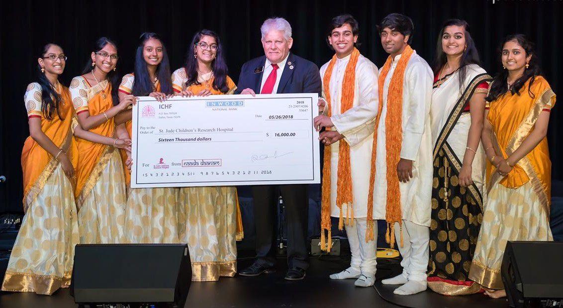 Eight organizers of a carnatic music benefit concert present a $16,000 check to Allen Mayor Steve Terrell. Photo by Prasad Golkonda.
