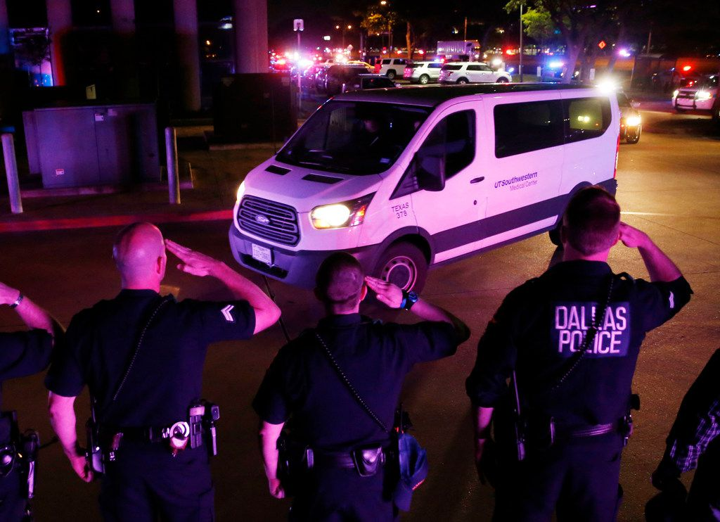 Dallas police officers salute as the van carrying the body of slain officer Rogelio Santander, Jr. travels to the Dallas County Medical Examiner's office in Dallas on Friday.