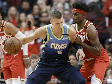 Dallas Mavericks forward Kristaps Porzingis (6) dribbles as Houston Rockets forward Danuel House Jr. defends during the second half of an NBA basketball game Friday, Jan. 31, 2020, in Houston.