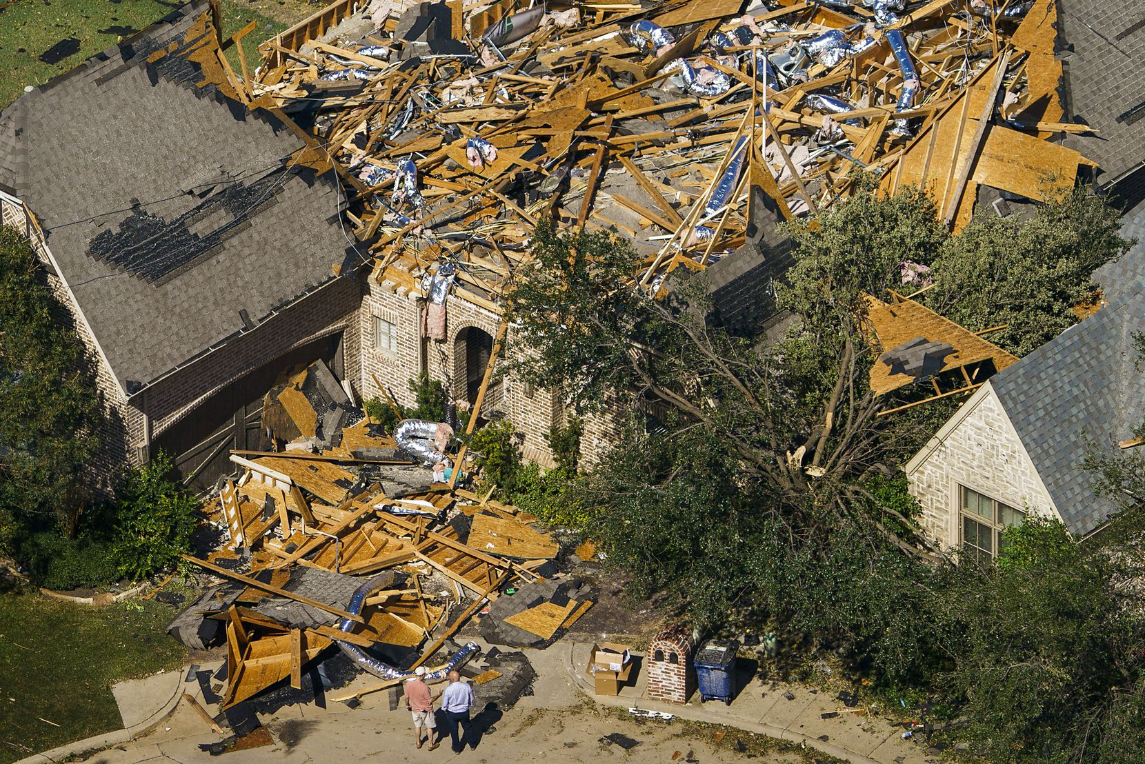 People survey tornado damage to a home near Walnut HIll Lane and Mash Lane on Monday, Oct. 21, 2019, in Dallas.