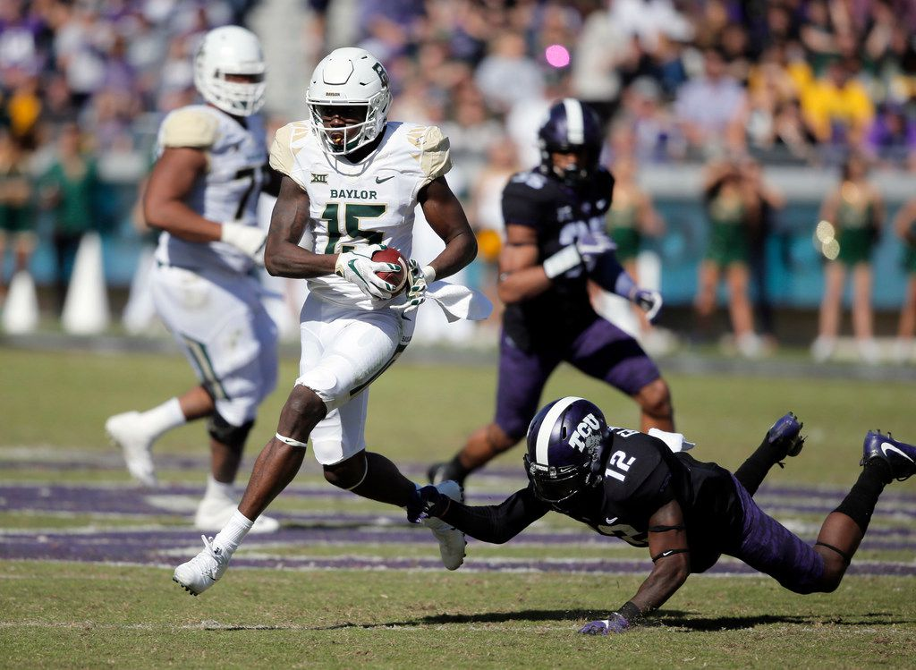 FILE - Baylor wide receiver Denzel Mims (15) evades a tackle from TCU cornerback Jeff Gladney (12) during the first half of an NCAA college football game, Friday, Nov. 24, 2017, in Fort Worth, Texas. TCU won 45-22. (AP Photo/Brandon Wade)