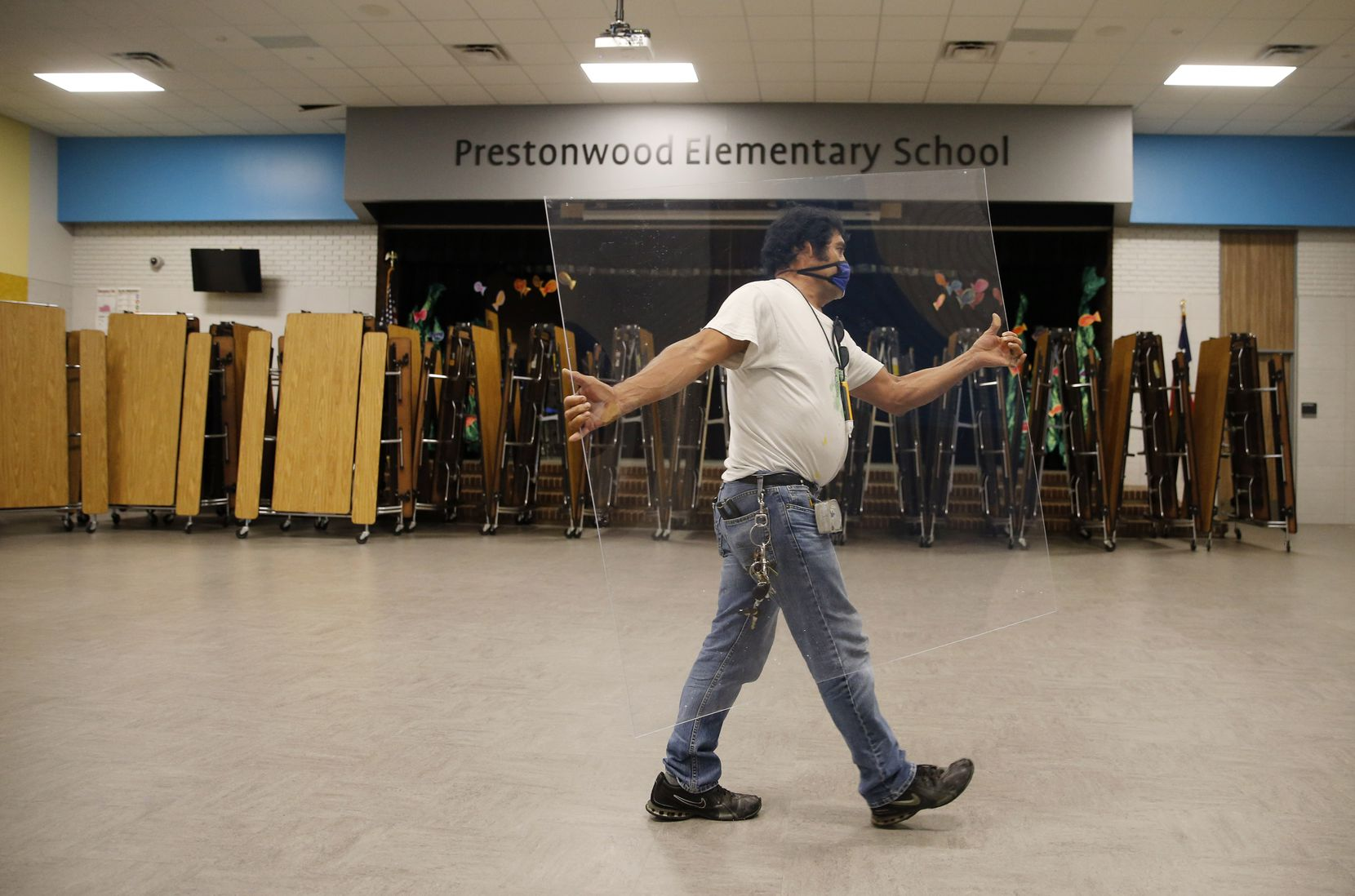 Daniel Limon, a Richardson ISD maintenance worker, carried a germ barrier to be installed in the cafeteria at Prestonwood Elementary in Dallas in July as schools prepared for students<EP>to return in a few weeks.