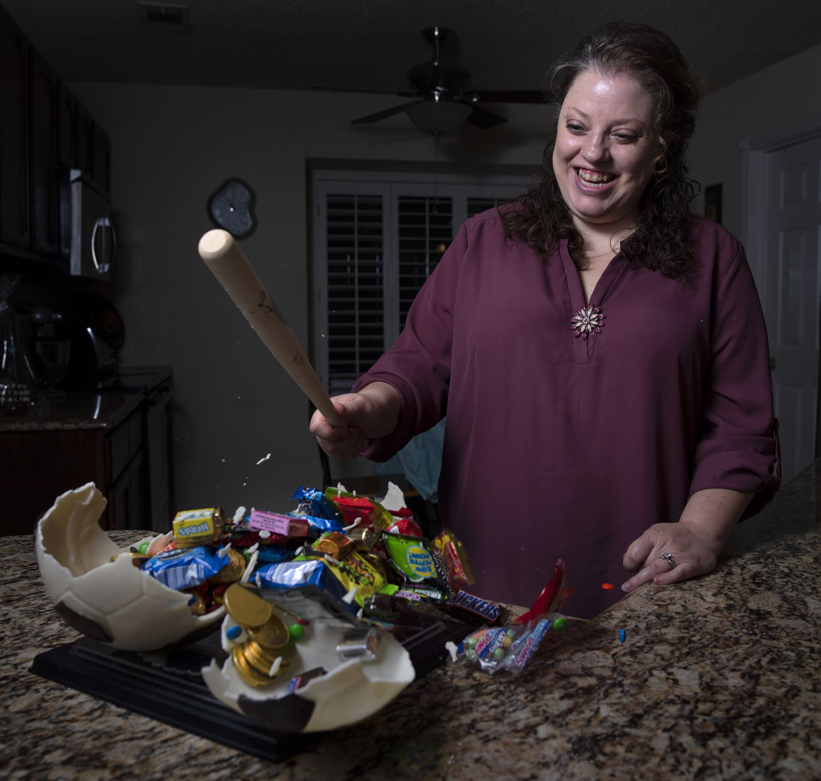Jill Baethge, owner of Kaboom Chocolaka, smashes a soccer ball made of white chocolate as candy treats spill out of it, at her home in Plano, March 13, 2020. The treats she makes are similar to Pinatas, but with an outer edible shell. Ben Torres/Special Contributor
