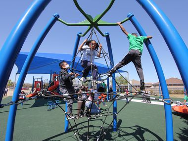 Children play on new playground equipment at Pearcy STEM Academy in Arlington ISD. The district plans to build similar playgrounds at every elementary school.