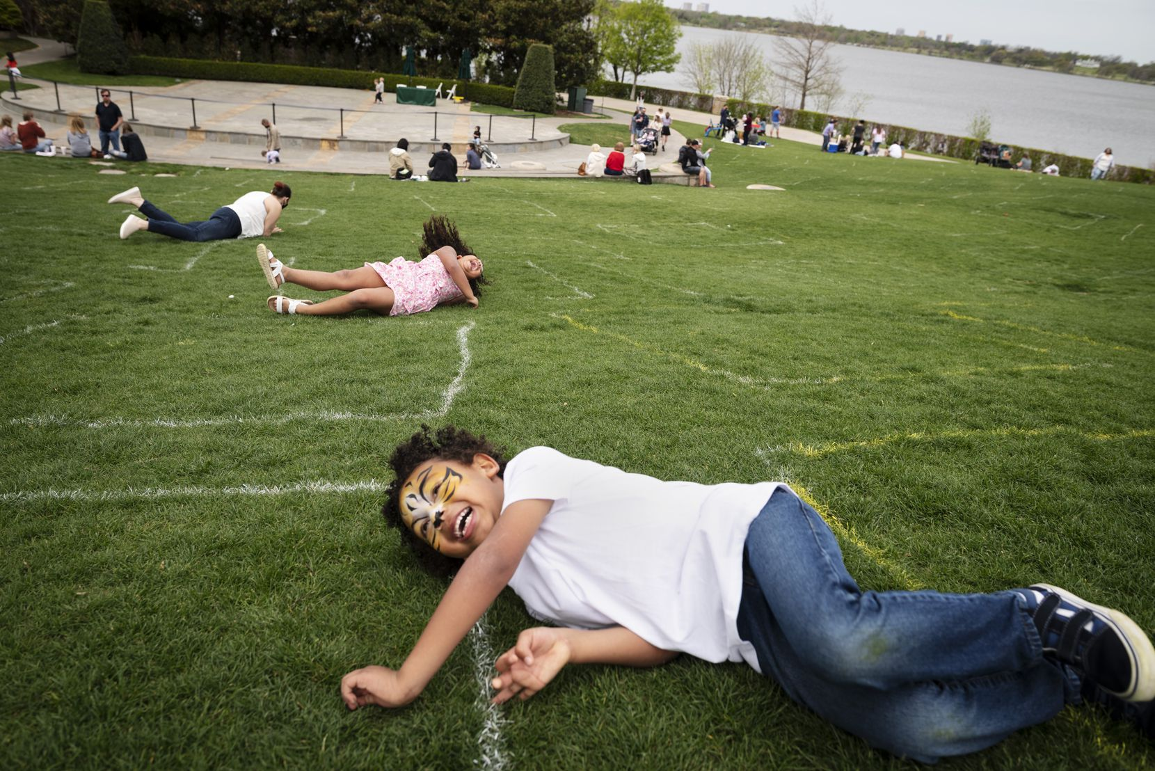 Kaniel Williams, 5, of Austin, rolls down a hill with his cousin Isadora Peña, 6, and mother Danielle Peña, as the families visited the Dallas Arboretum for Easter weekend, on Saturday, April 03, 2021 in Dallas.