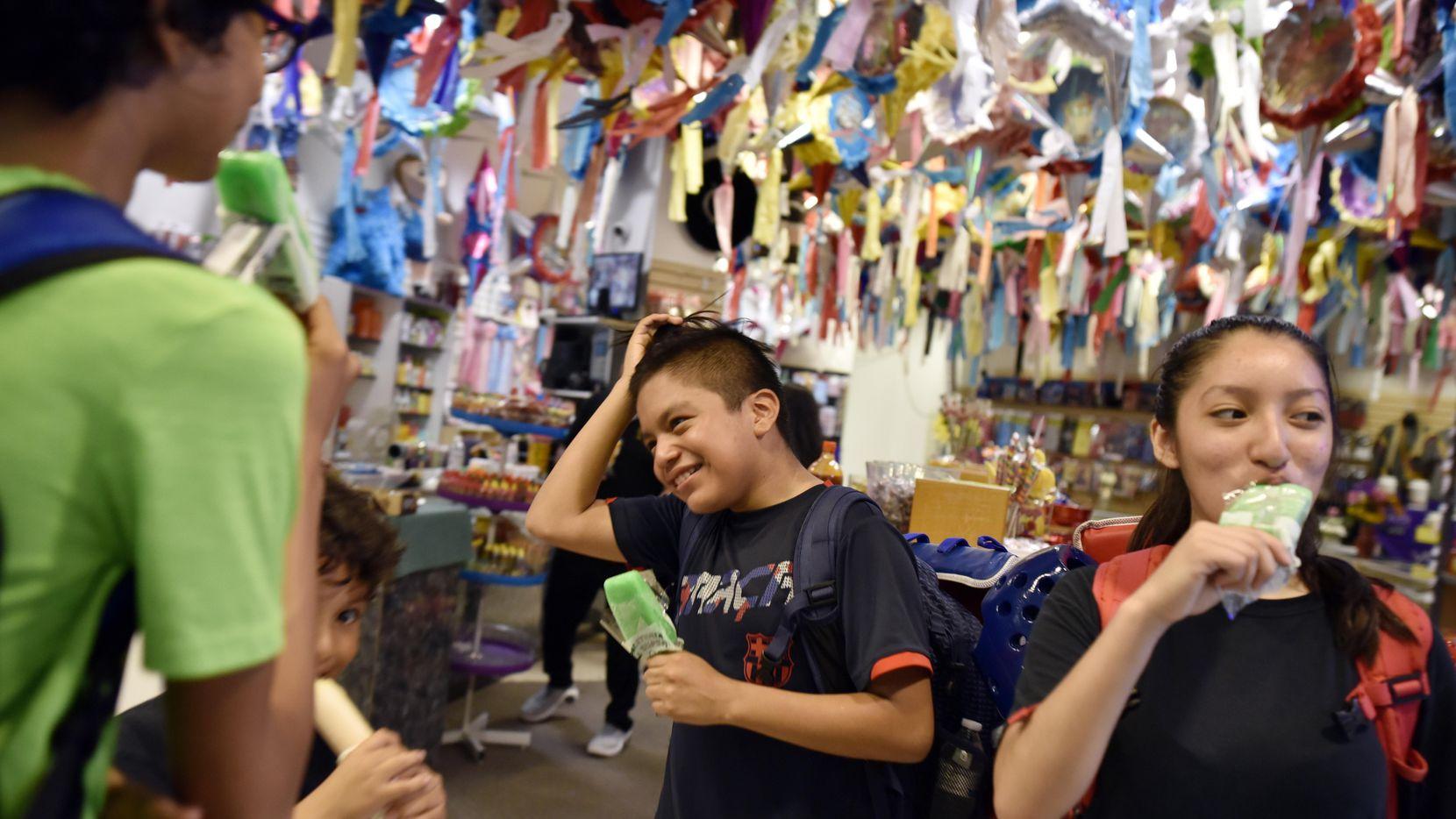 Jesse Pérez, de 12 años, y Karla Montoya, de 14, disfrutan de paletas de limón en el Rincón Hispano, en el Valley View Mall. La tienda de dulces es uno de los pocos locales que permanece abierto.  ——-  Nery Hernández (segunda desde la izq.) platica con su clientela en las afueras del Rincón Hispano, una de las últimas tiendas abiertas en el Valley View Mall. BEN TORRES/AL DÍA