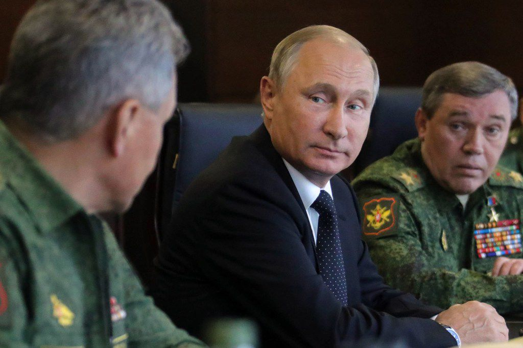 Russian President Vladimir Putin (C), accompanied by Defence Minister Sergei Shoigu (L) and Chief of the General Staff Valery Gerasimov (R), watches the joint Zapad-2017 (West-2017) Russian military exercises with Belarus at the Luzhsky training ground in the Leningrad region on September 18, 2017.