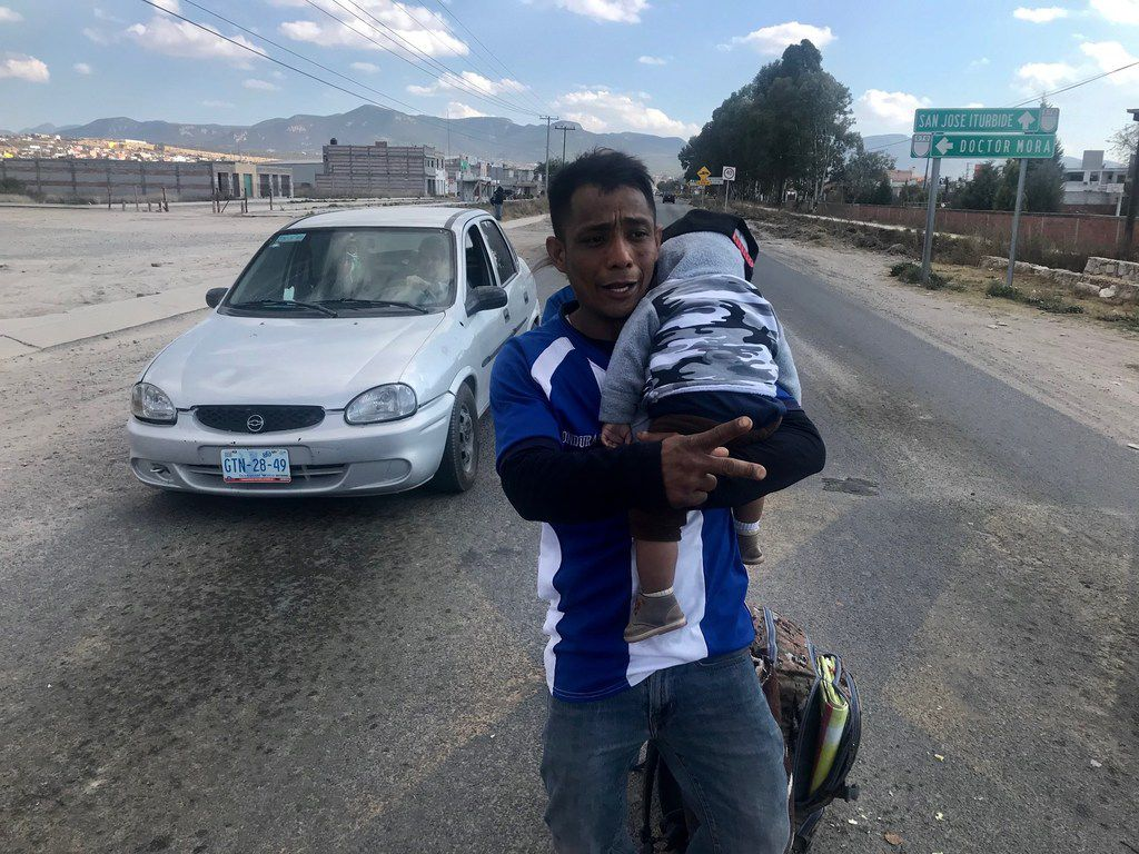 Jonathan David Cardenas, 32, with 8-month-old son Julio Cesar, walked along a main thoroughfare in Guanajuato, Mexico, the week of Jan. 22, 2019. They were asking for handouts from motorists and were part of a caravan that originated in San Pedro Sula, Honduras, headed for Houston.