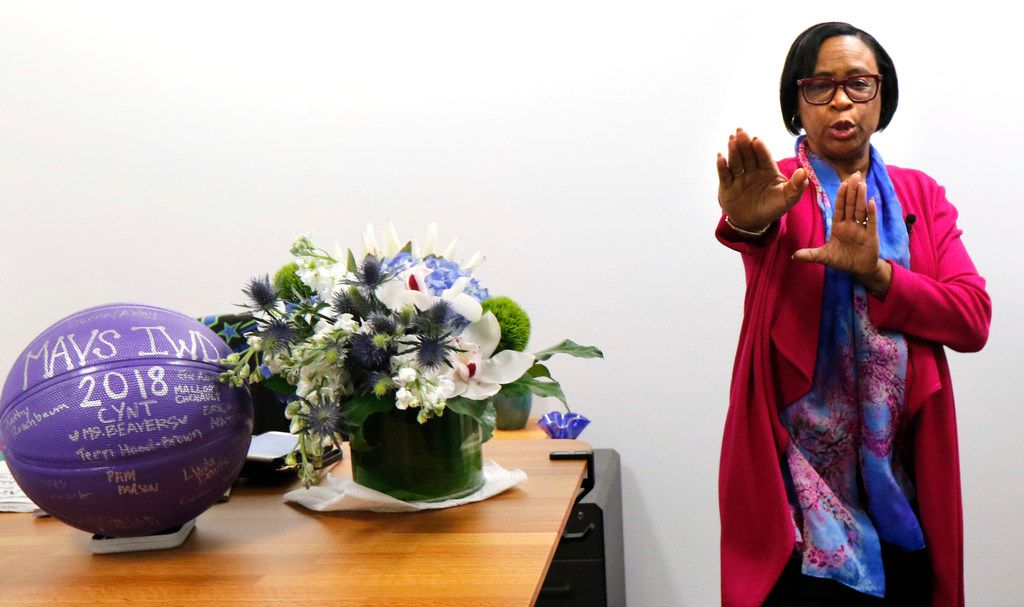 "Dallas Mavericks interim CEO Cynt Marshall demonstrates in her office how she would cheer and dance during football games where she attended  University of California-Berkeley, Friday, March 16, 2018. After 36 years, Cynt left AT&T after achieving ""rock star"" status, according to co-workers. She left to launch a consulting firm focused in part on leadership and inclusion. (David Woo/The Dallas Morning News)"