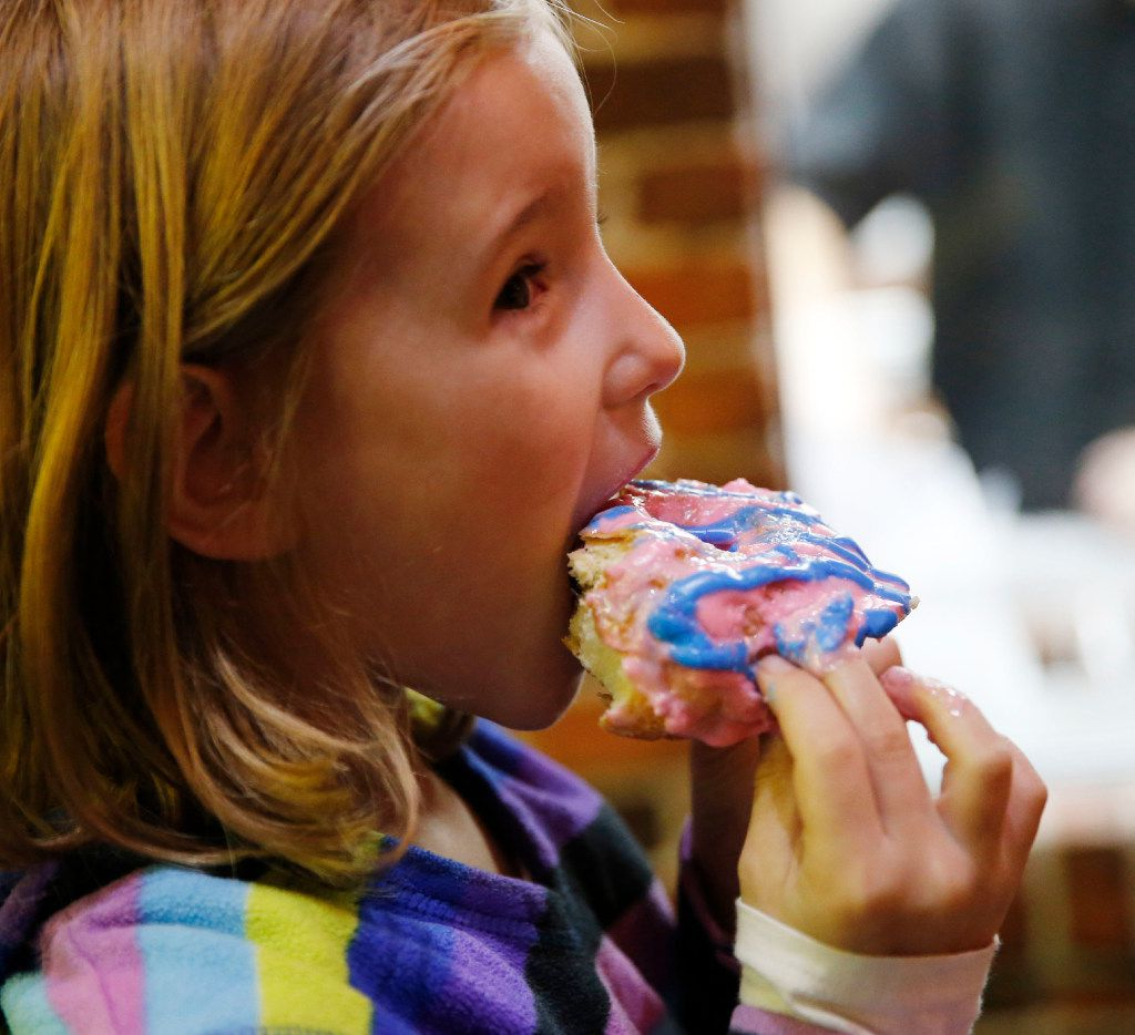 Cosette Ellis, 7 of Frisco takes a bite of a cotton candy donut during the grand opening at Hurts Donut Co. in Frisco on Wednesday, January 25, 2017. This is Hurts Donut Co.'s first Texas location.