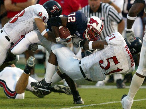 SMU's #32 Keylon Kincade gets tackled by TX Tech's#28 Ryan Aycock and #51 Lawrence Flugence during the second quarter of action Saturday night at SMU's Gerald J. Ford Stadium on the campus of SMU.