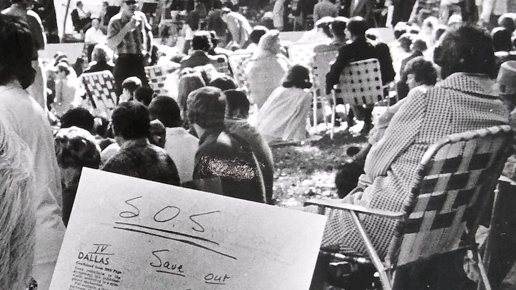 "In 1974, a Dallas Symphony Orchestra concert-goer reviews one of the ""SOS: Save Our Symphony"" appeals distributed among the 7,500-person Lee Park crowd, during a concert at the park in Dallas."