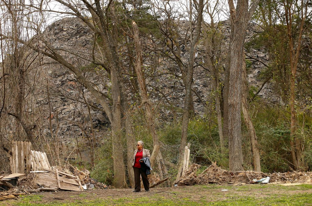 Homeowner Marsha Jackson walks past flood-damaged fencing bordering a large hill of recycled roof shingles near SH 310 and Interstate 20 in southern Dallas on Jan. 31, 2019.
