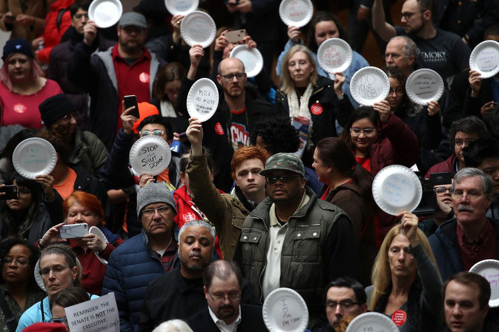Furloughed federal workers and supporters protested the partial government shutdown inside the Hart Senate Office Building Jan. 23 in Washington, D.C.The protesters wrote messages on paper plates.