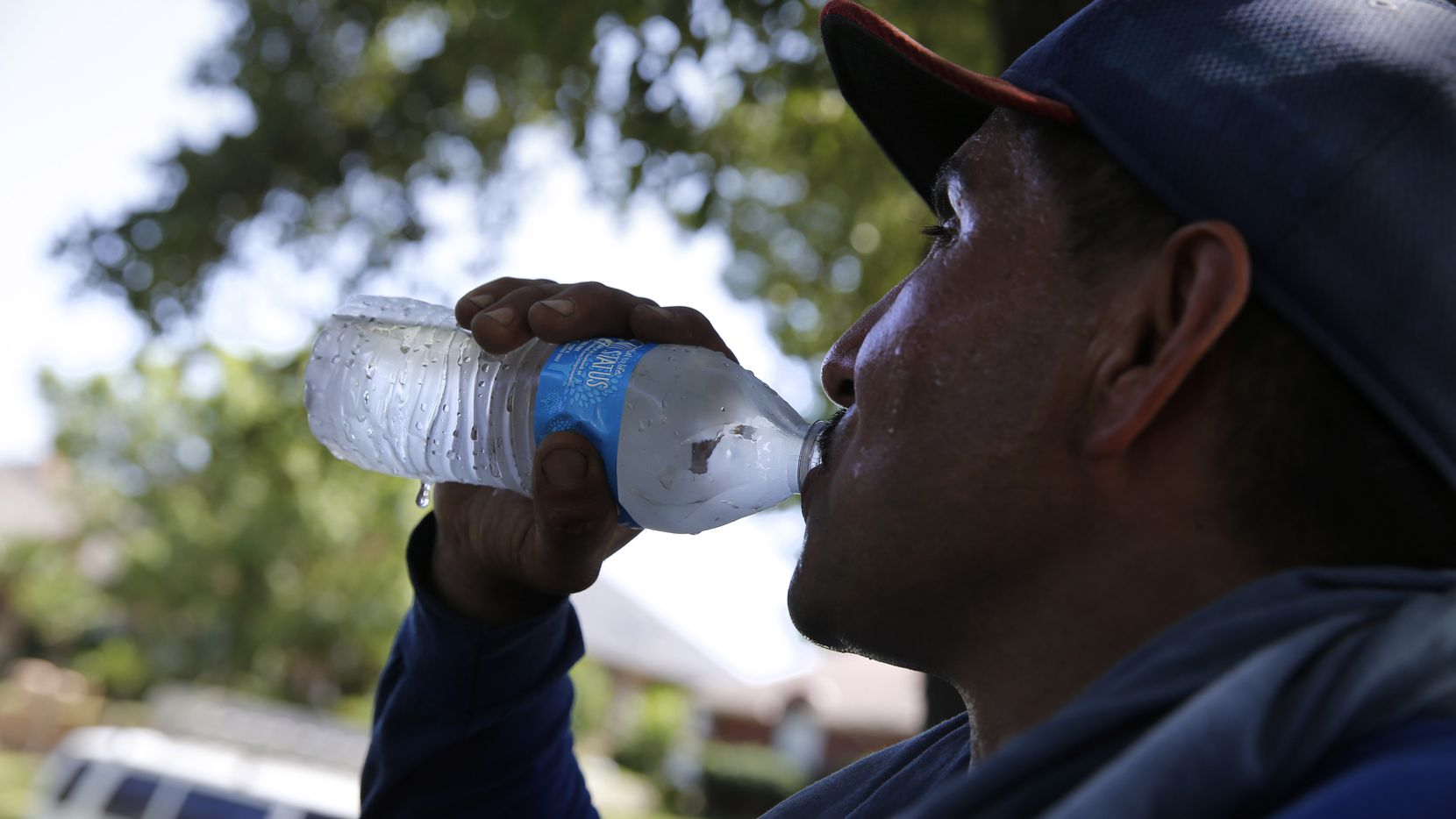 Alejandro Cervantes drinks water on a break as roofer put shingles on a house in Arlington, Texas on July 19, 2018.