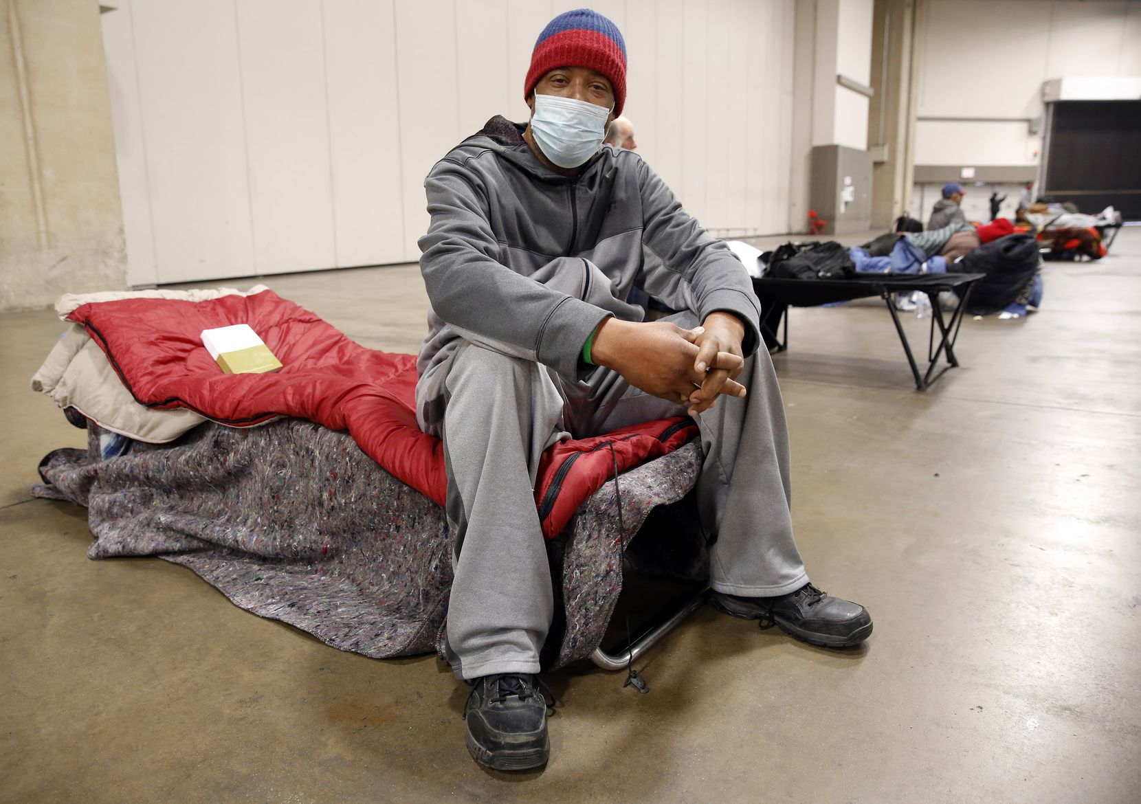 Pierre Scott, a 59 year-old guest and volunteer at a warming center run by OurCalling, is pictured on his socially-distanced cot at the Kay Bailey Hutchison Convention Center in Dallas, Tuesday, February 16, 2021. Scott like a lot of other folks, found refuge from the overnight sub-zero temperatures. (Tom Fox/The Dallas Morning News)