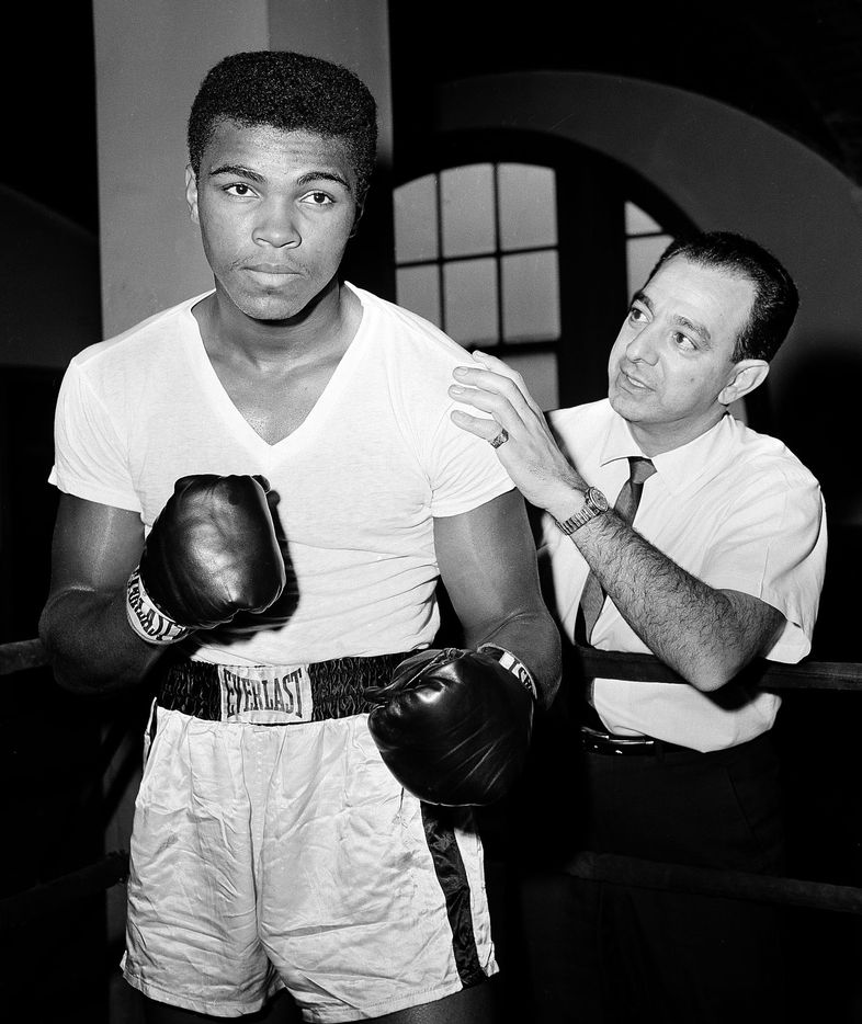 In this Feb. 8, 1962, file photo, a young Muhammad Ali, left, stands with his trainer Angelo Dundee at City Parks Gym in New York.