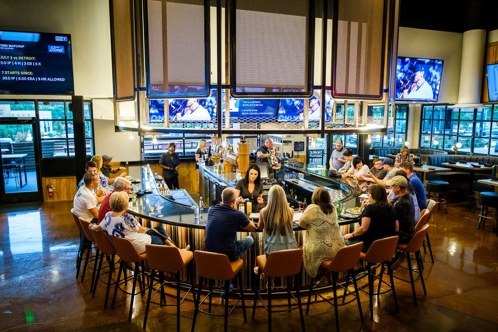"""Televisions surround a bar at Sidecar Social, a new two-story """"interactive social lounge"""" in Addison."""