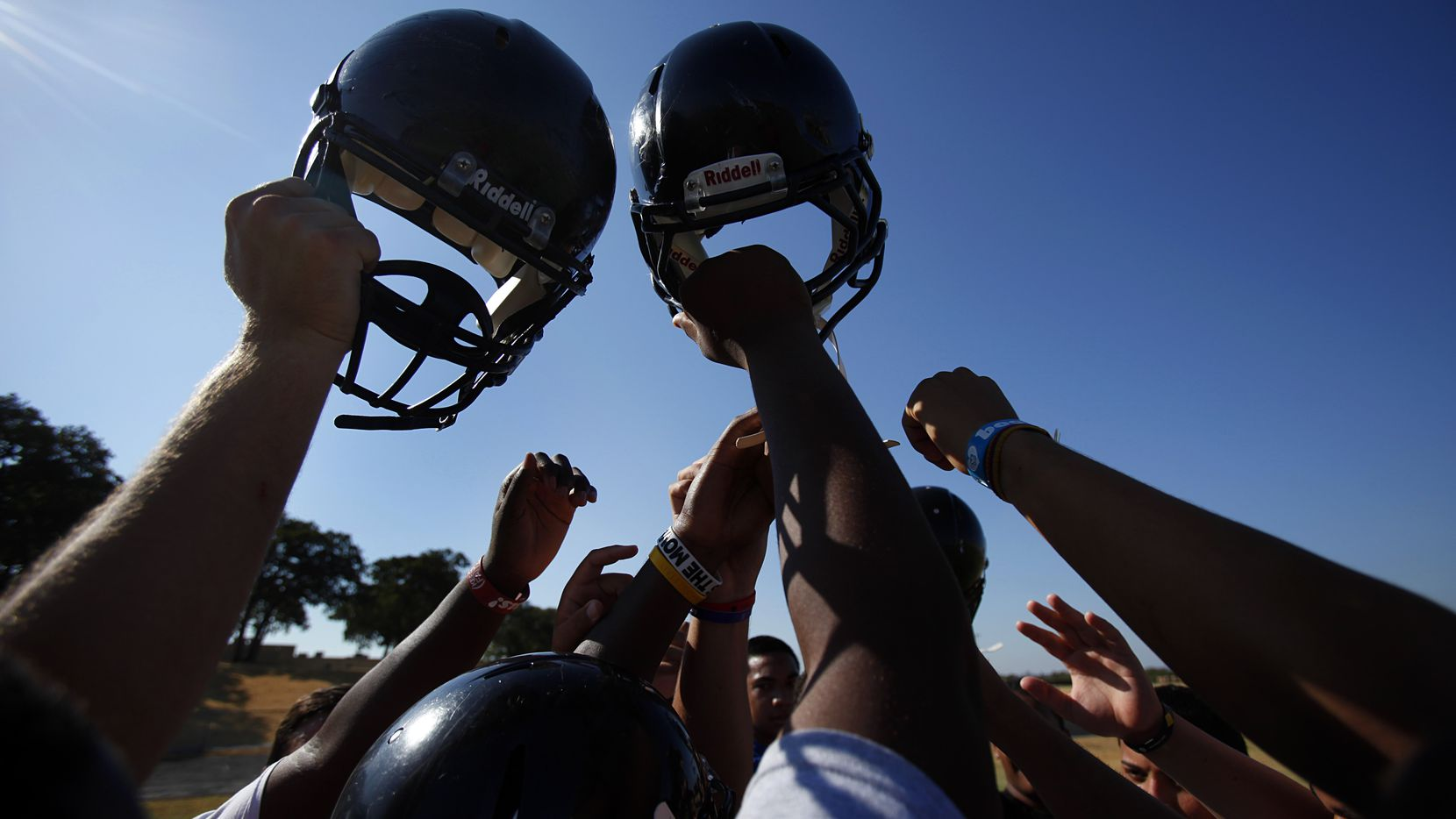 Euless Trinity players raise their helmets as the team's practice concludes. It was the first day of high school football practice for schools, including Euless Trinity, who had spring practices.  The players went through a morning workout, August 8, 2011.