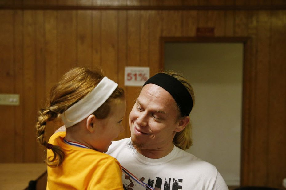 Professional wrestler Andy Dalton of Irving holds his 5-year-old daughter, Mia, before he goes out for a match at the Sherman Elks Lodge.