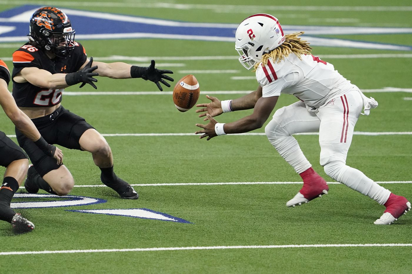 Crosby Deniquez Dunn (2) reaches to recover his own fumble against Aledo Sammy Steffe (26) during the first half of the Class 5A Division II state football championship game at AT&T Stadium on Friday, Jan. 15, 2021, in Arlington. (Smiley N. Pool/The Dallas Morning News)
