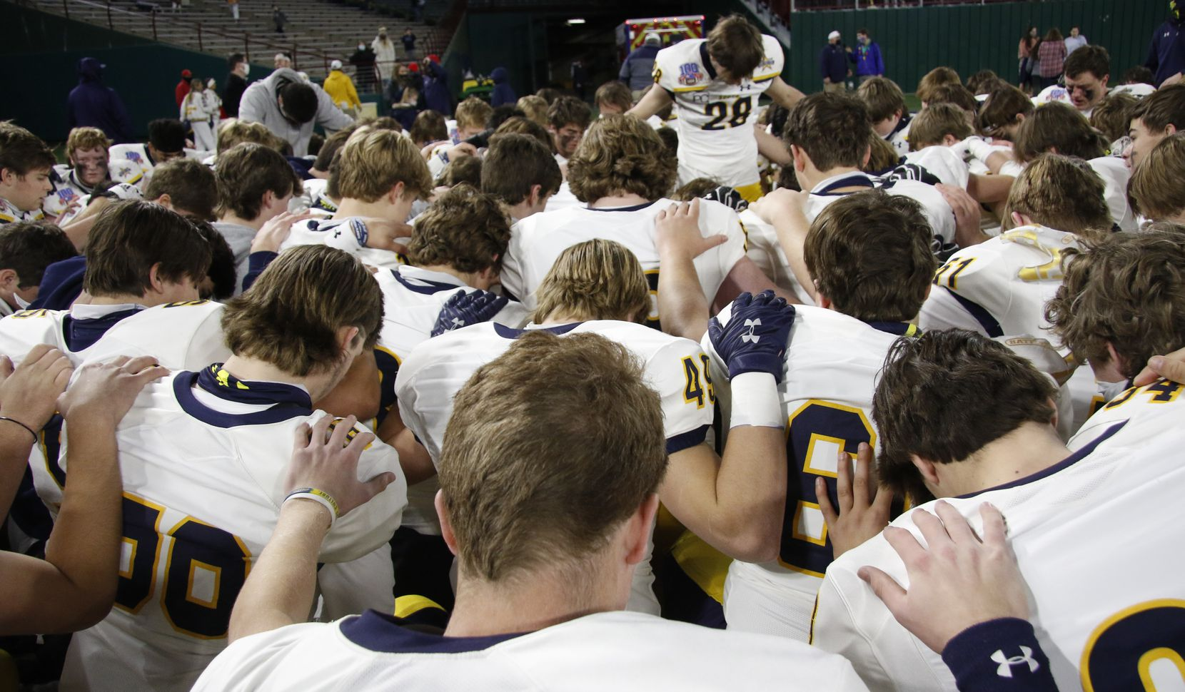 Highland Park Scots players take a knee as they are led by defensive back Ford Frazar (28) in a team prayer following their 30-20 victory over Frisco Lone Star to advance. The two teams played their Class 5A Division l Region ll semifinal football playoff game held at Globe Life Park in Arlington on December 24, 2020. (Steve Hamm/ Special Contributor)