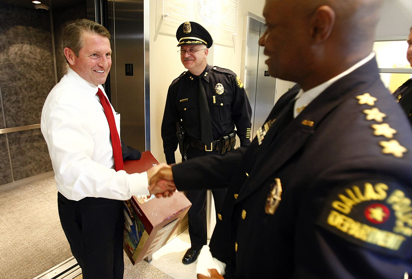 On his way of out of police headquarters for the last time, outgoing Dallas police chief David Kunkle (left) ran into newly sworn police chief David Brown (right) as he stepped off the elevator. The two shook hands, wished each other well and then parted ways - Kunkle to the parking garage, Brown to the police chief's office, Tuesday, May 4, 2010. Kunkle was carrying a margarita machine, a parting gift from a staff member. In background, center, is Assistant Police Chief Daniel Garcia, who was one of the finalists for Kunkle's job.
