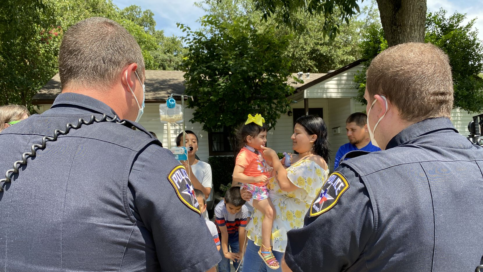 Irving police officers Adam Vanderveer (left) and Jon Long visit with Sarai Tirado on Tuesday, July 7, 2020, at her home following a parade with vehicles from the Irving police and fire departments. Sarai, 4, recently returned home from the hospital where she was recovering after unsecured furniture fell on her.